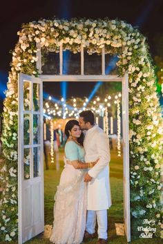 Candid Couple Shot - Beautiful Entrance with Floral Themed Decor | WedMeGood | Bride in a Blue Pastel Blouse with a Pink Pastel Lehenga and Net Dupatta and the Groom in a White Sherwani #wedmegood #indianbride #indiangroom #coupleshot #decor #DIY