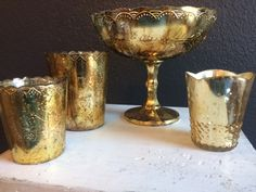 distressed gold urn for look A. Small gold mercury cups to be paired with antique bud vases for look B
