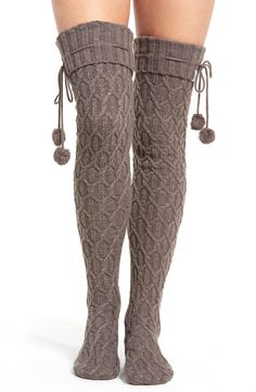 Metallic threads sparkle throughout the cozy and chunky cable knit of festive socks ready for lounging and layering in a tall over-the-knee fit fastened with swingy pompom ties.