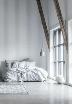 bed - white décor white walls white flooring -wooden beams - a bed built for cuddles - pendant lighting - minimalist