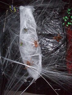 Chicken wire formed into a basic cocoon shape then wrapped with quilt batting painted black, then wrapped in various layers of spider webbing.  Place a battery-operated bumble ball (dog toy) in the back and it will shake slightly.  With the spiders added to the outside