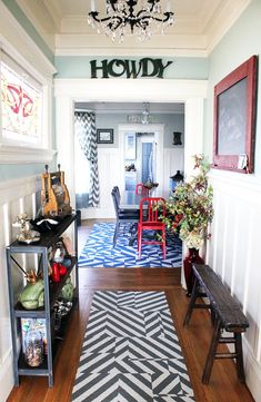 """Add originality to your home with an entryway that pops with eclectic details, from the chandelier to the """"Howdy"""" sign to the patterned rugs. Color, texture, and pattern are what add personality to a space."""