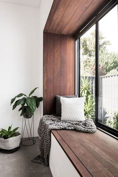 This modern bedroom has a wood framed window seat that overlooks the garden.