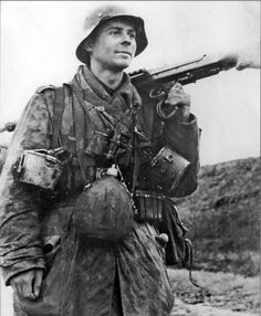 Young German grenadier somewhere on the Eastern Front. He's carrying drum magazines for his MSG plus bandoleers, a military water flask, and binoculars.