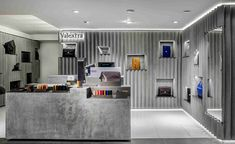 at the center, a geometrical podium is complemented with partitions at different heights, and bespoke boxes that house small leather goods.