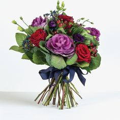 Romance- In this gorgeous bouquet, which spills over with bright red roses and purple brassica, we have tried to truly capture the essence of romance.