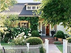 What I love:  - white pickett fence, overgrown white flowers, and vine on porch!