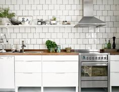 white, modern cabinets; white tile, grey grout; raw wood; stainless steel