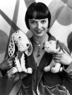 American silent film star Louise Brooks with her mascots, Dismal Desmond (left) and Bonzo (right). ca. 1920's. ☚