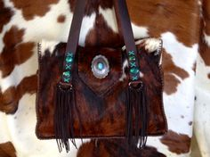 The Buckaroo Tote: cowhide, suede fringe, turquoise and a one of a kind piece on the purse flap. gowestdesigns.us