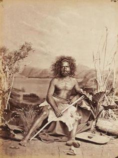 Original 'John Lindt' Full-length Frontal Sepia Photograph of a Bearded Man seated with Scarification and wearing a Fur Loin Cloth and holding a Stick. A Shield sits at his feet