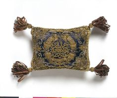 Pin cushion, England, 1660-1699 T.54-1978, V&A Museum This pin cushion characterises the style of embroidery of the 1660s and 1670s. The preference is for mainly metal threads worked over thick padding, giving a heavy three-dimensional effect. The embroidery design is quite architectural, incorporating stylised floral patterns.