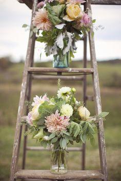"""Idée déco : des escabeaux à l'entrée de la salle avec fleurs et bougies pour un style """"rustique"""""""
