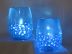 Simple & affordable centerpiece idea = submersible LED lights with gel marbles in multiple smaller glass containers: http://www.flashingblinkylights.com/ledsubmersiblecraftlights-c-114_462.html