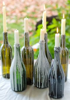Going for a colonial look? You could wedge some taper candles into the mouths of the bottles and let the wax run down.