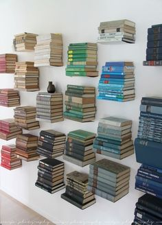 Floating bookshelves arranged by color. Someone let their OCD flag fly and we love it!