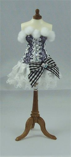Swan Noir. Exquisite basque in black & white on dainty resin mannequin 5 inches tall (1/12th scale). Bodice is made of black fairy dust trimmed with pure white dainty braid, finished with a pure white pom pom neckline. Cute pure white satin/lace skirt completed with black & white gingham bows & Swarovski aurora borealis crystals.