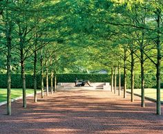 Rows of locusts in an Ohio garden lead directly to a bronze sculpture by (one of all-time favourite artist/sculptors) Henry Moore.  (Architectural Digest)