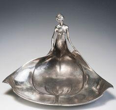 Orivit-Metallwarenfabrik, Cologne. Art Nouveau figural calling card tray, 1904.  Silver-plated pewter. Marked: ORIVIT 2638. H. 21 cm; L. 31.5 cm.