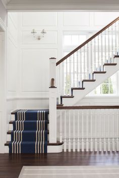 White, navy and wood staircase with a striped runner and paneling. Not a huge fan of these sconces at first, but they are growing on me.