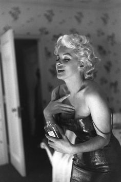 marilyn monroe, famously a no.5 fan, pictured with a bottle of the scent