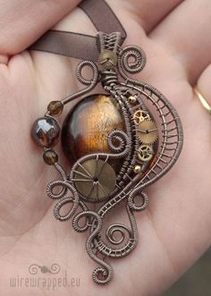 Victorian styled Steampunk pendant with polished glass, wire wrapping and watch parts.: