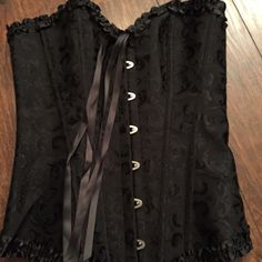 Small black corset NWOT Black corset w/ ruffle edge detail. Size small, would say closer to extra small. New without tags, never worn as it does not fit me. Tops Camisoles