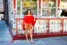 Rosie Assoulin top, Yves Saint Laurent shorts, Michael Kors sandals  Enjoy said sleeve that looks like bat wing perched atop glass soda bottles.  I call this one: former teacher of the history of architecture, enjoying a Staycation in Little Italy, while she attempts to distinguish the graffiti from the art and her bagged lunch from her bagged bag. See next slide.  Atea Oceanie x Man Repeller button down shirt, Maryam Nassir Zadeh bra, Rosie Assoulin pants, Oscar de la Renta shoes, Lucy Fo