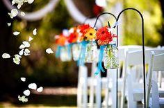 mason jars filled with flowers on shephard hooks for isle