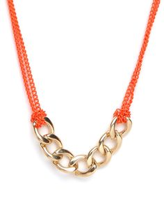 """what a cool combination - This eclectic necklaces adds a shot of cool with to the standard chain link necklace. In a rather Surrealist move, it casts the chunky gold chains as the """"pendant"""" and sets them against a series of smaller tangelo-colored links."""