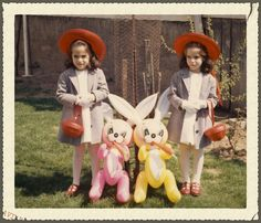 Vintage Easter snapshot photo of pretty twin girls wearing bonnets and posing with bunny rabbits, circa 1960s.