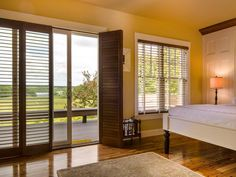 Dark wood plantation shutters provide privacy in the master bedroom while allowing light to stream in through the sliding doors and windows.