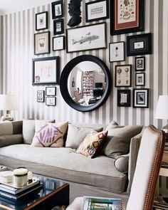 Salón con espejo en la pared y acertada disposición de los cuadros.