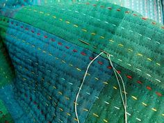 machine quilted lots of closely spaced rows, of varying widths, followed by long rows of multi colored hand-stitching
