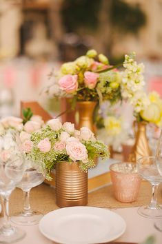 easy centerpiece idea- spray paint cans gold and fill with pretty flowers http://www.weddingchicks.com/2013/09/20/vintage-destination-wedding/