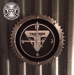 A clock made from a recycled Triumph 48 tooth sprocket and the face is etched aluminum with black paint on the background.