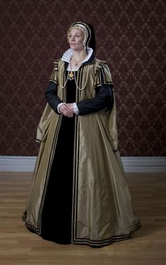 A silk taffeta loose gown over a black velvet kirtle. Worn with a French hood.  I'm more than impressed with this Tudor re-creation!