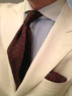 Cream jacket, light blue shirt with white dress stripes, brown tie with red medallions