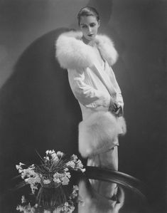 Vogue 1929 Model, Marion Morehouse, standing beside a table set with a vase of flowers, and wearing a white crepe wrap with white fox collar and hem band, by Augustabernard. (Photo by Edward Steichen/Condé Nast via Getty Images) Vintage Fur, Mode Vintage, Vintage Chanel, Vintage Love, Vintage Photos, Vintage Glamour, Vintage Style, Vintage Photographs, Edward Steichen