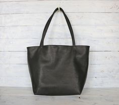 New/// Large size Simple, Supple, Soft & light-weight Black cow leather tote bag! This Simple & Stylish leather tote bag to be the perfect all day tote bag!    Roomy enough for all your daily essentials and would work great all year round. The leather handles are strong enough to carry your laptop, Books and fit comfortably over your shoulder. The bag is fully lined with thick Black canvas with 5 interior pockets.