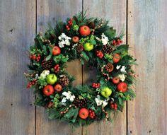une couronne de Noël verte décorée de pommes de pin, pommes et baies rouges