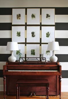 our entry with piano, botanical prints and striped walls (home tour at emilyaclark.com)