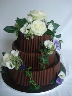milk chocolate wedding cake decorated with cigarellos chocolate and fresh flowers