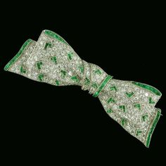 Art Deco diamond bow-brooch accentuated with calibré-cut emerald chevron motifs…