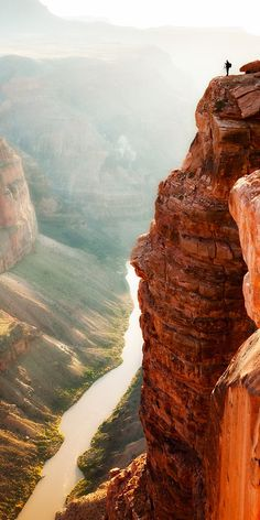 A photographer stands on the edge of Grand Canyon at Toroweap.