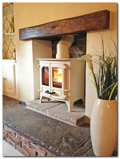 Charnwood Island oak fireplace beam, brick rear wall and reclaimed Yorkshire stone hearth. Love the hearth :) Wood Burning Stove Insert, Wood Stove Surround, Insert Stove, Wood Burning Stove Corner, Fireplace Beam, Fireplaces, Fireplace Inserts, Wood Stove Fireplace Insert, Cream Fireplace