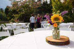 simple summer wedding centerpiece with sunflower in Mason jar on woodcut