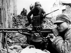 88 - A Chinese machine gunner takes aim in the ruins of...