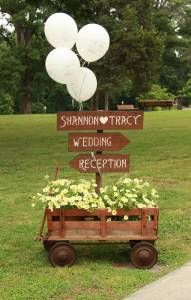 In front of a wedding sign, put some potted flowers in a cute wagon.