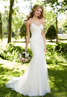 This dramatic, yet elegant, lace and tulle over Lustre satin wedding gown from Stella York features sexy spaghetti straps, a sweetheart bodice fitted to just below the hips, and an eye-catching tulle and lace layered train. The back has an easy-close zipper that remains hidden under lace-covered buttons. The Knot provides price estimates to give you a general idea of the cost of a dress. Please visit retailers in your area for exact pricing. Prices will vary by region.